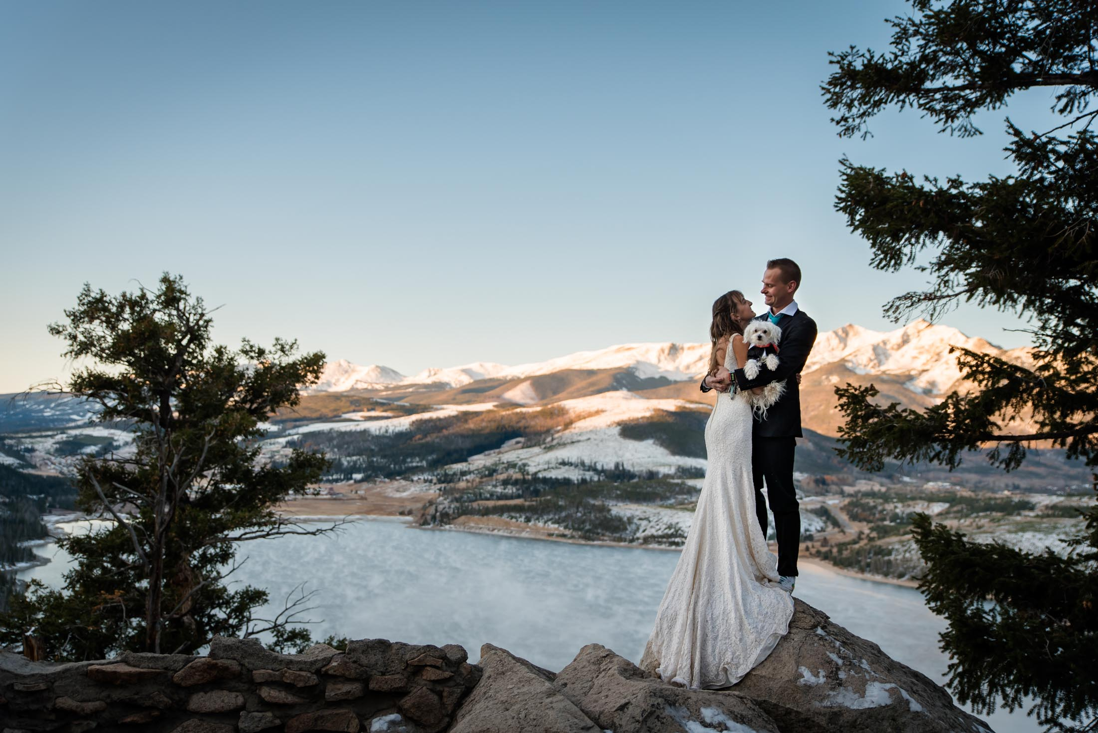 Couple snuggles on a mountain top together with their dog at their sunrise elopement in Colorado