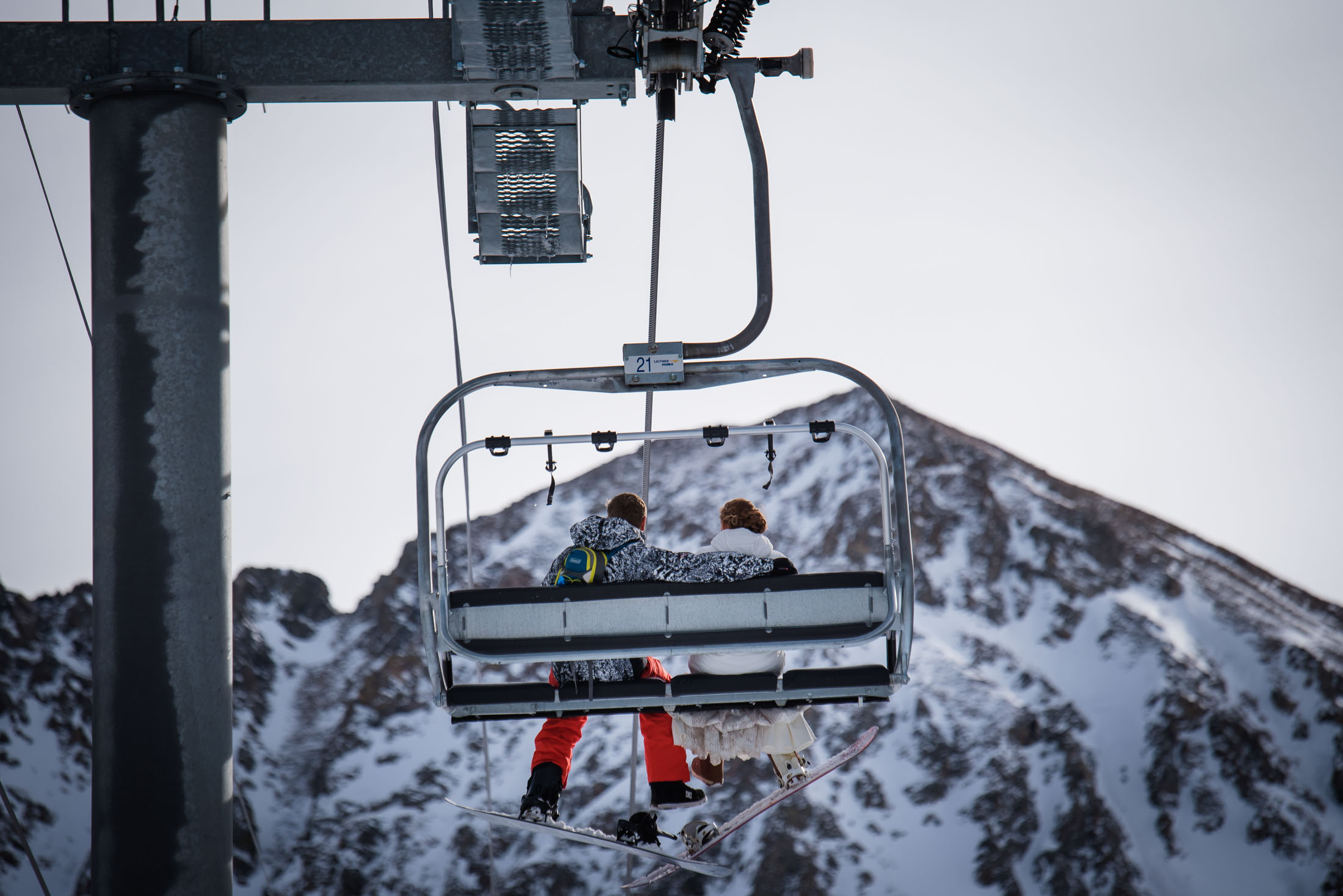 Couple together on ski lift for their snowboarding elopement at Arapahoe Basin Resort
