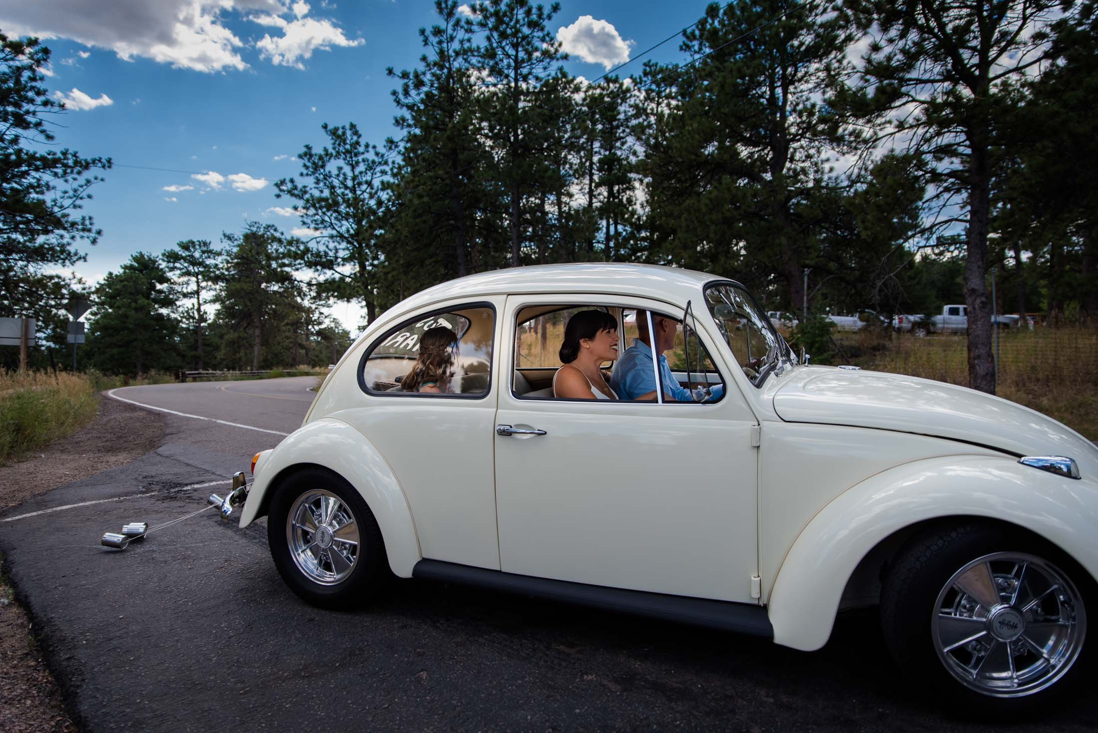 Couple in Colorado takes off in white vintage volkswagon beetle after their elopement