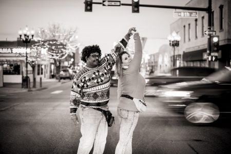 Couple poses together in the streets of Denver in 80s styled clothes for their awkward 80s engagement session