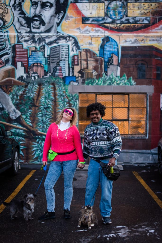 Couple poses together in Denver in 80s styled clothes for their awkward 80s engagement session