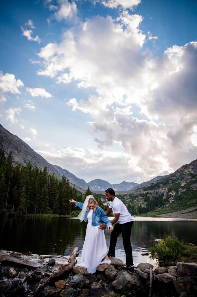 a groom helps his bride cross a stream at blue lakes in Breckenridge after their elopement