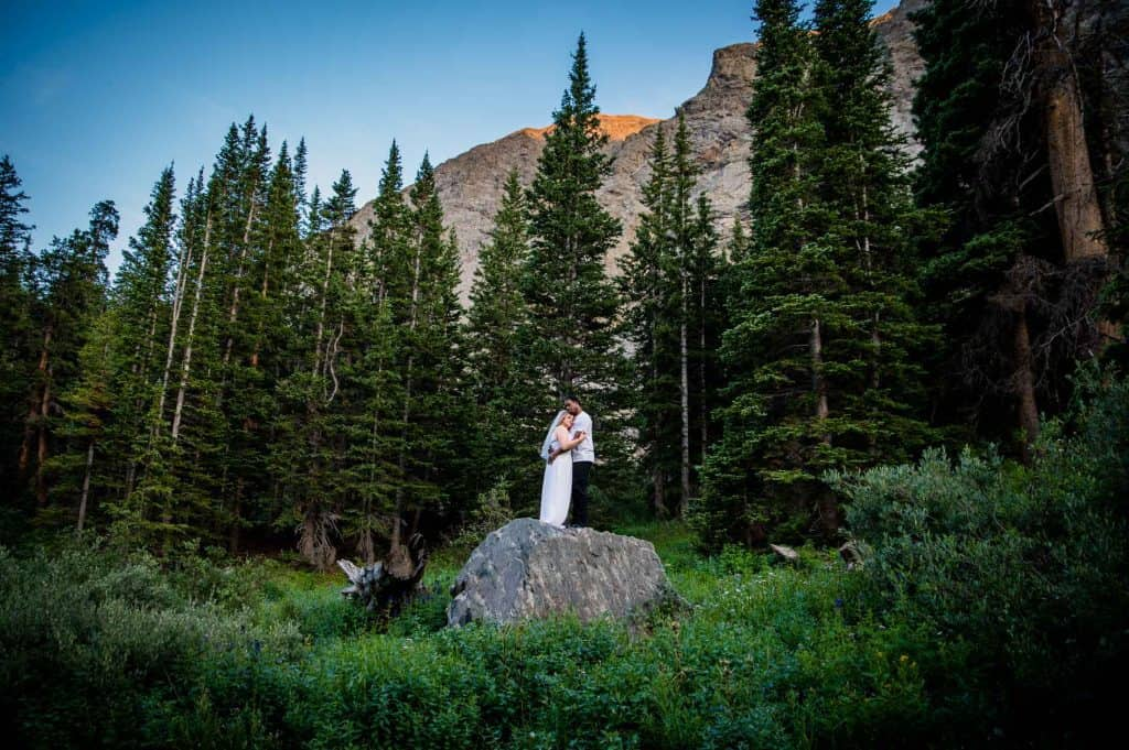 a bride and groom embrace on a big boulder in a field of wildflowers after their elopement in Breckenridge