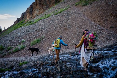 a bride and groom cross a stream after their elopement on top of blue lakes in ridgway, colorado