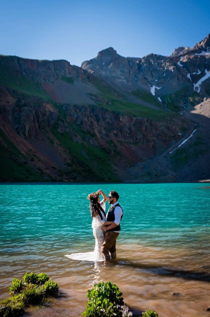 a bride and groom stand in the lower blue lake in Ridgway underneath Sneffels and Dallas Peak