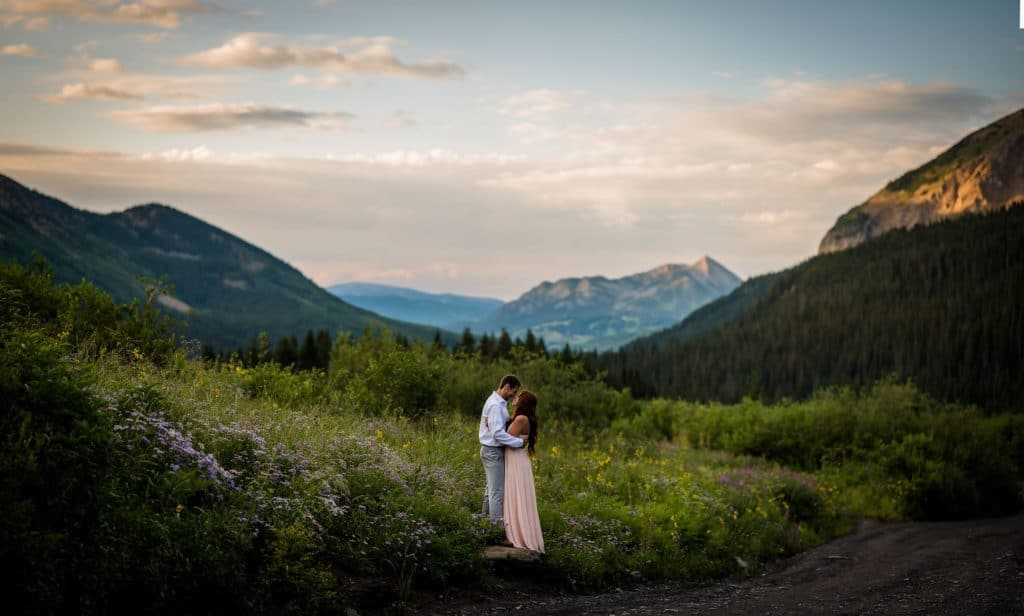 a couple embraces in the wildflowers at sunrise with Mt Crested Butte in the background for their adventure anniversary photography session.