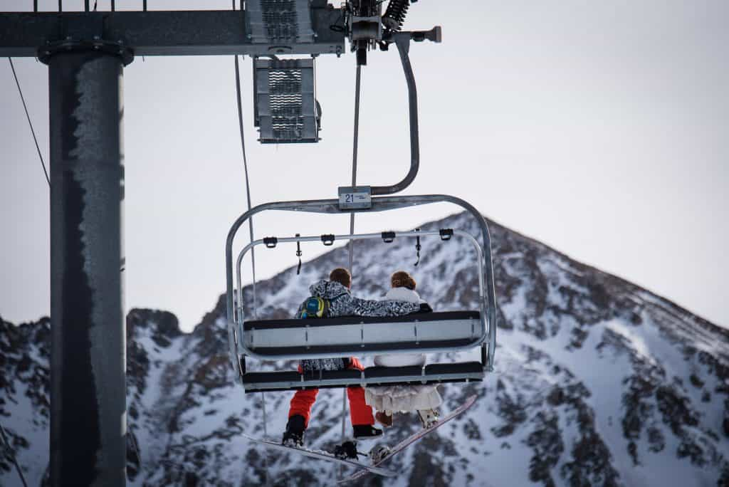 Couple riding the ski lift in their wedding attire at A-Basin to snowboard before their mid-mountain elopement ceremony at the Black Canyon Lodge