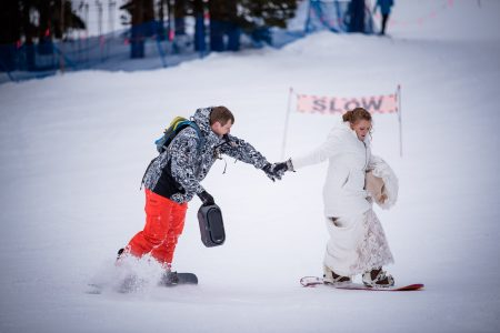 A couple snowboards down the slope after their elopement ceremony at Arapahoe Basin Ski Area's Black Mountain Lodge
