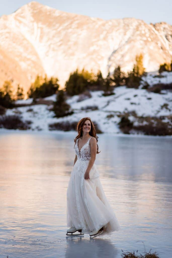 a bride ice skates on a frozen alpine lake at her elopement in Colorado