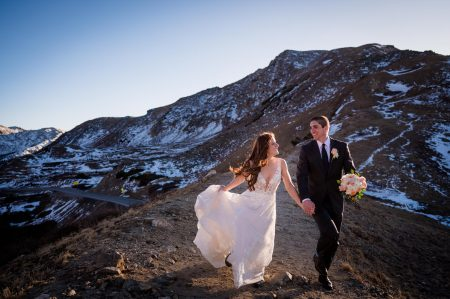 A couple running along a ridge on top of Loveland Pass in Colorado