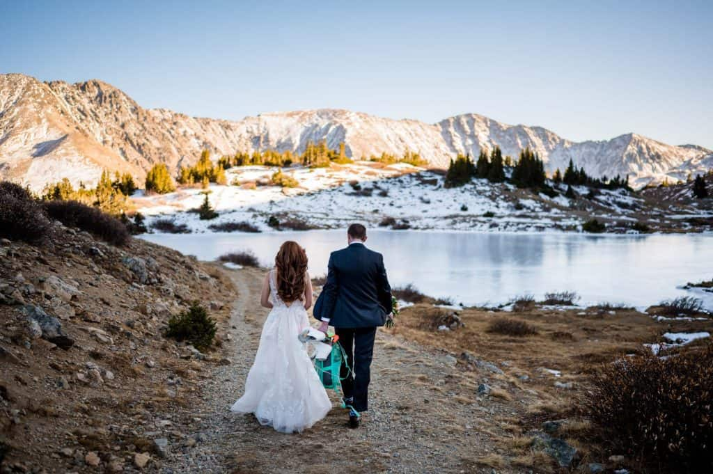A groom holds his bride's ice skates as they walk towards a frozen backcountry alpine lake in the Arapahoe National Forest in Colorado
