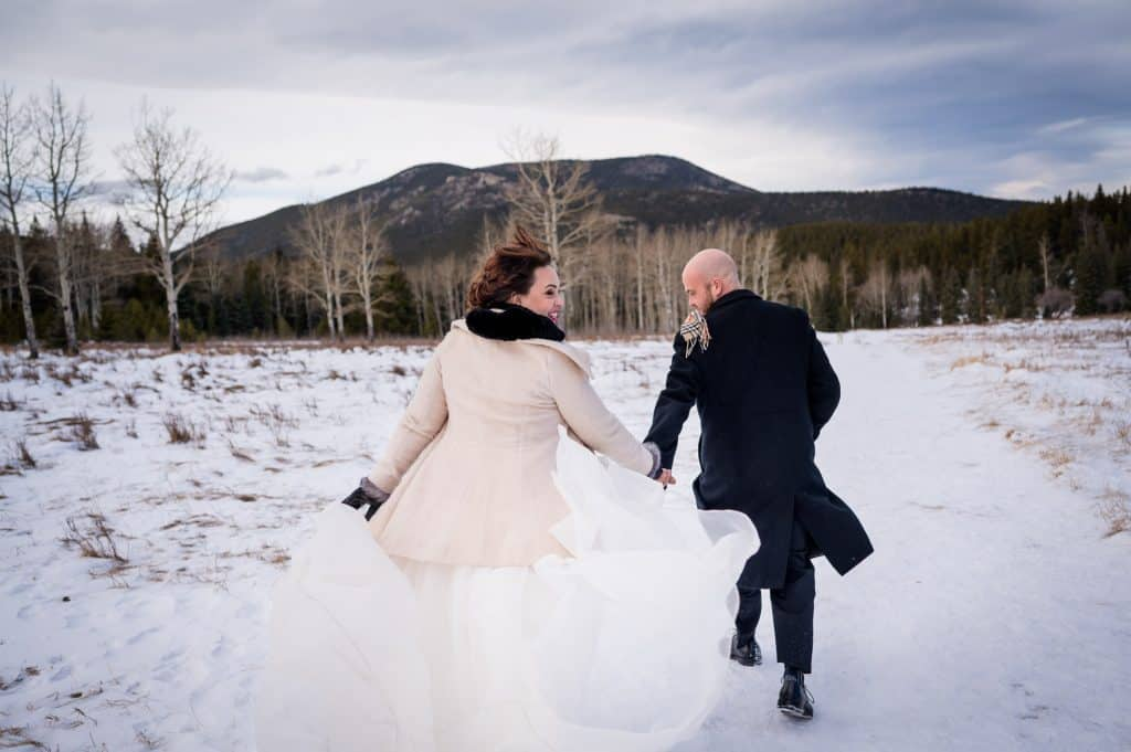 A bride and groom hiking in the mountains on a windy day for their Colorado elopement