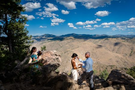 A groom wipes tears away from his Bride's face during their mountain top elopement ceremony in Golden, Colorado