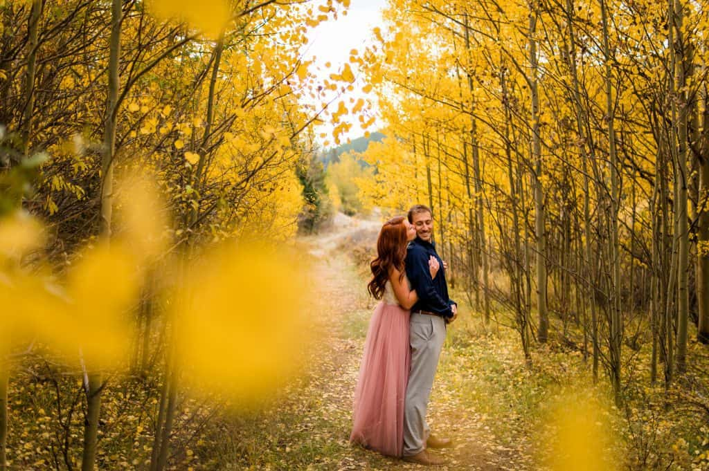 A couple snuggles up in an aspen grove in the Fall in Colorado mountains