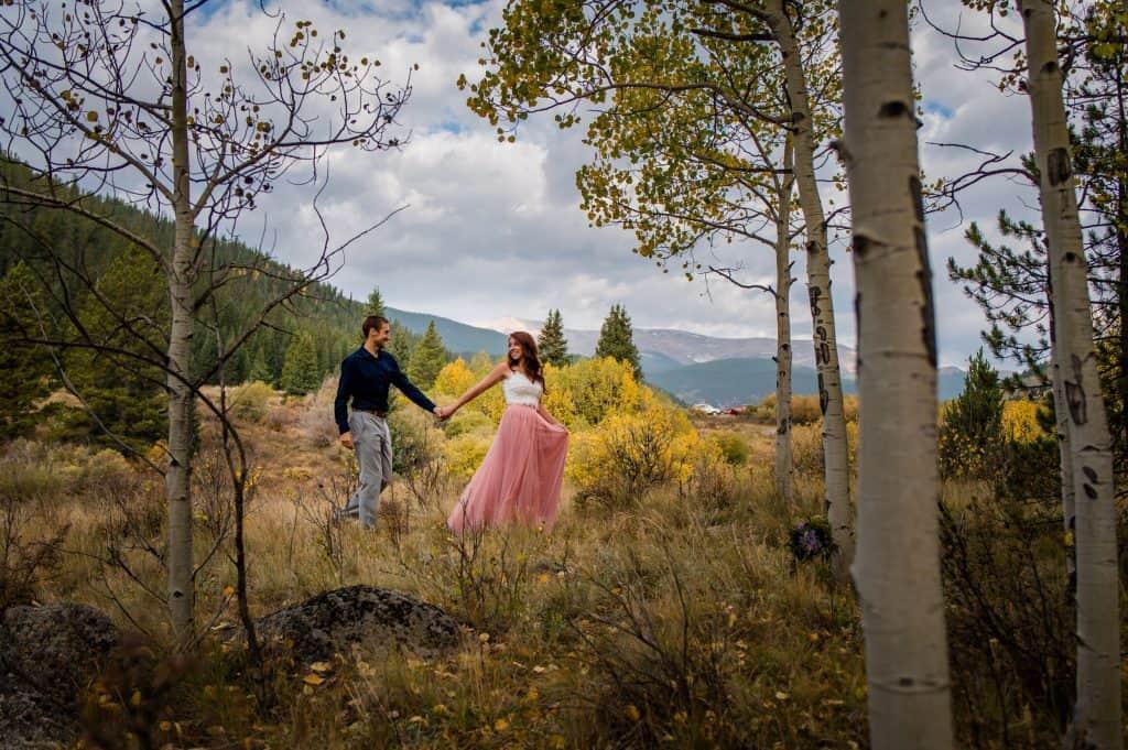 A couple walks through an aspen field i