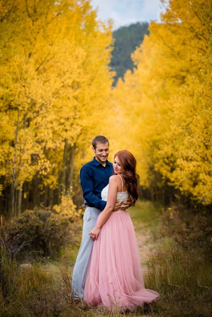 A groom looks at his bride as they stand in a golden aspen grove in Colorado after their Fall mountain elopement near Guanella Pass
