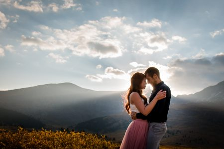 A couple embraces in the mountains during a beautiful and dramatic sunrise shining behind them