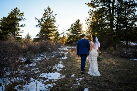 The bride and groom walk together in the sun after their outdoor elopement ceremony in Colorado