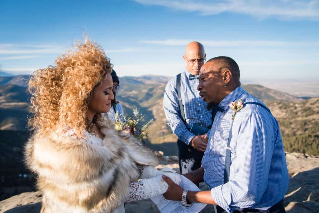 A couple exchanges vows on top of a windy mountain in Colorado