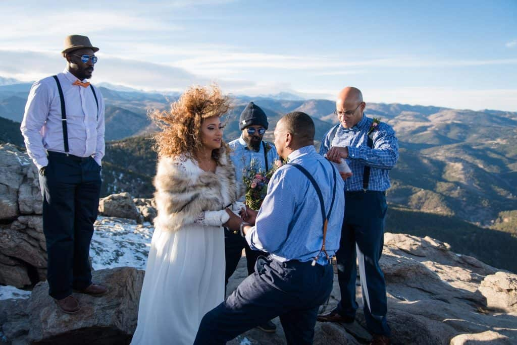 a bipoc couple stands on a mountain top at their windy winter elopement ceremony in Boulder, Colorado