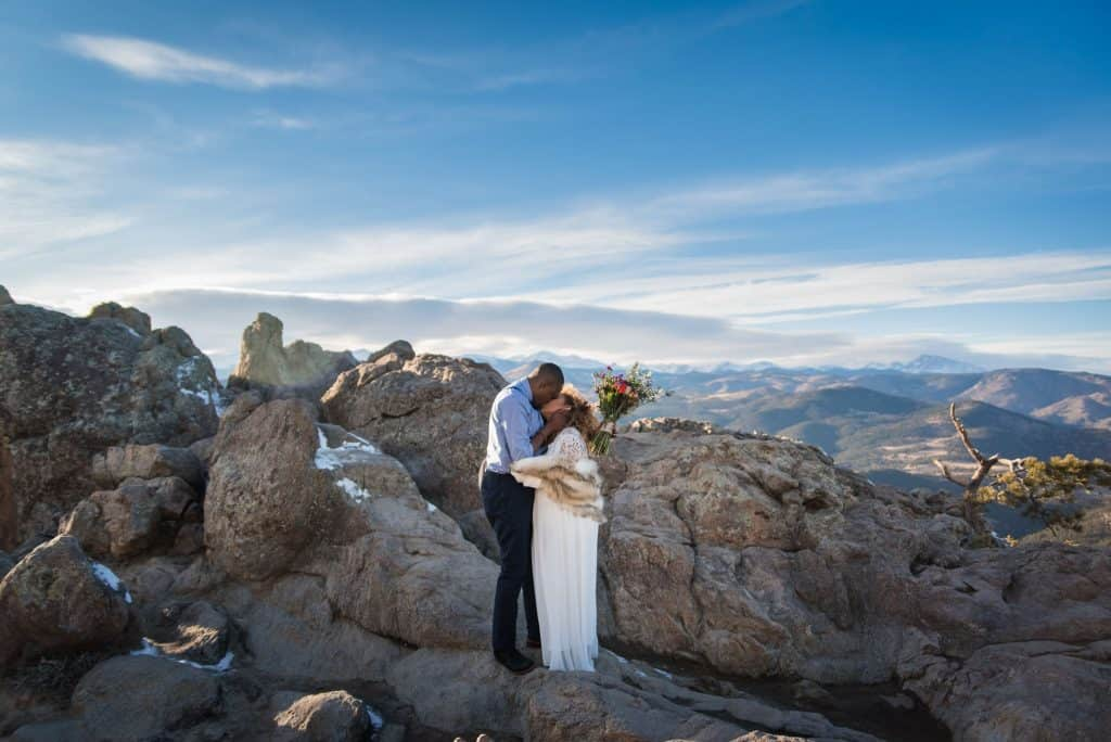 BIPOC couple kissing on top of a mountain in Colorado where they just eloped on a gorgeous winter day in February