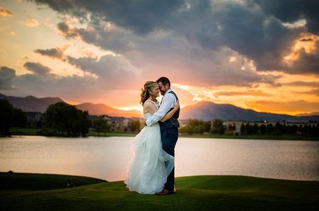 A couple embraces in front of a lake with mountains in the background during a stormy orange and grey sunset at the Barn at Raccoon Creek wedding venue in Colorado
