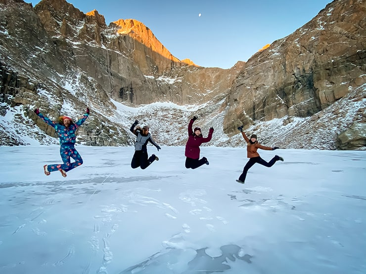 4 ladies jumping on the frozen Chasm Lake underneath an alpenglow lit Longs Peak after hiking up in the dark to catch sunrise on the lake