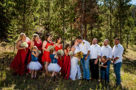 a bridal party gets close for photos at their friends private cabin wedding in Tabernash, Colorado