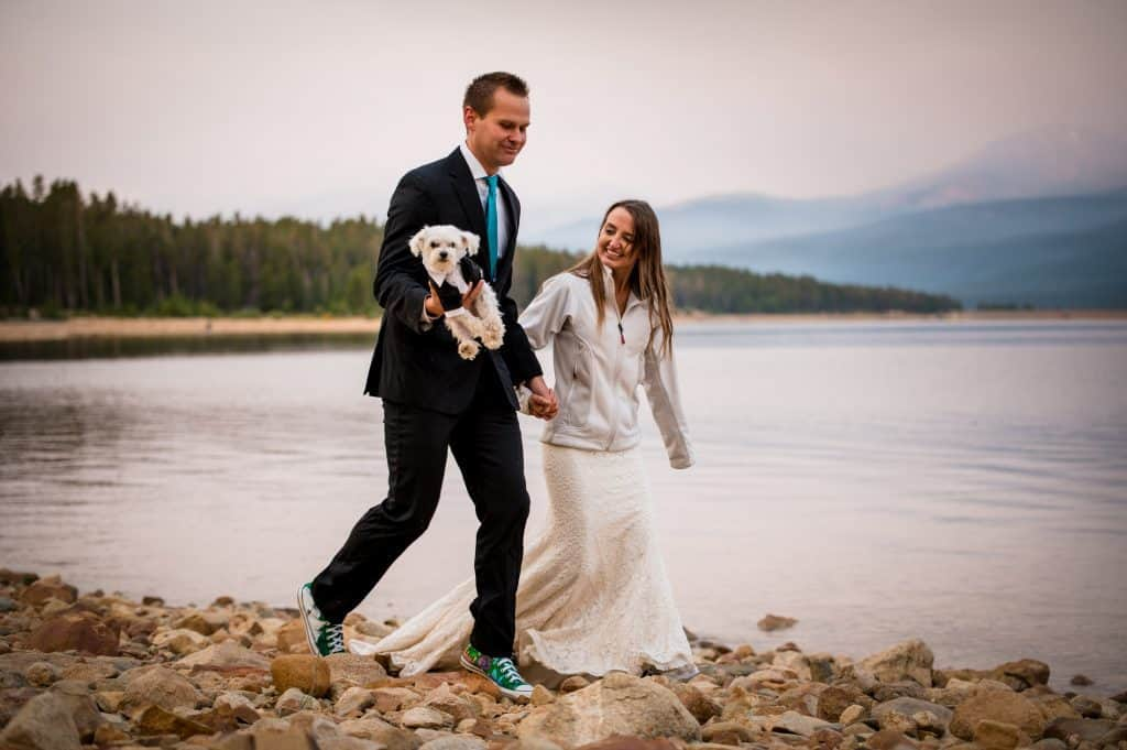A bride and groom walk hand in hand along the rocky shores of Turquoise Lake in Leadville, Colorado after their sunrise elopement on the beach.