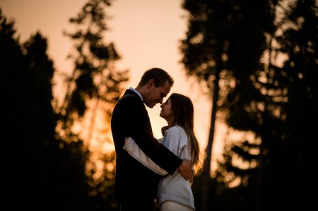 A couple stands face to face under a firey sunrise sky and silhouette pine trees after their adventure elopement at Turquoise Lake in Colorado