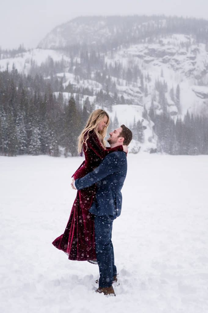 A man picks up his fiance at their winter engagement photography session in Estes Park RMNP
