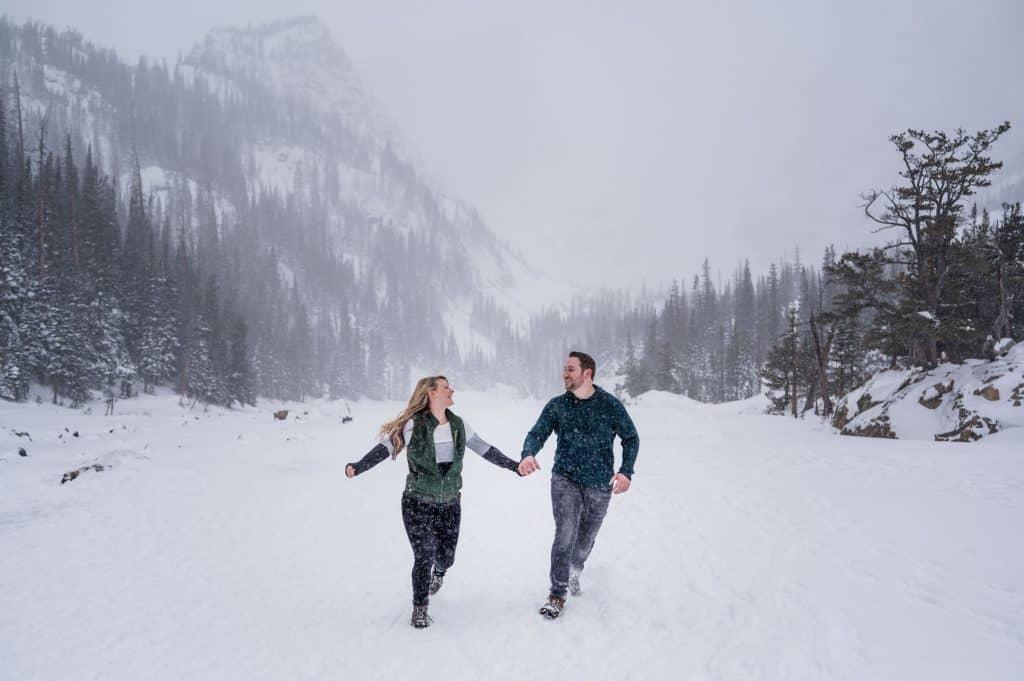 A couple runs through a blizzard on a frozen lake in RMNP for their engagement photos