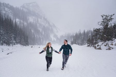 A couple runs through a blizzard on a frozen lake in RMNP for their engagement photos