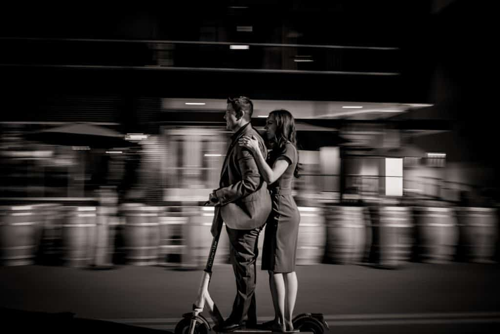 an lgbtq couple rides a scooter together through RiNo at night